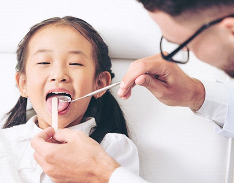 child getting their mouth examined by a dentist