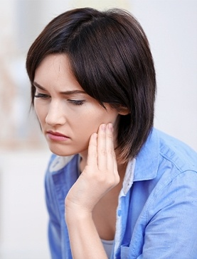 Woman in pain holding cheek