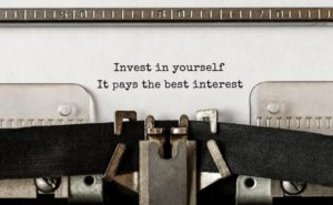"a typewriter that has a piece of paper in it that says ""Invest in yourself. It pays the best interest."""